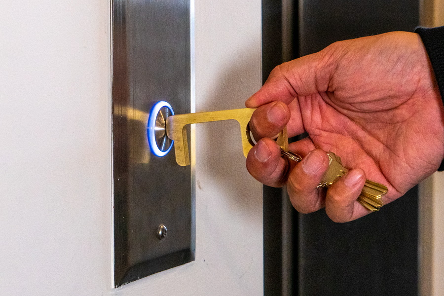 A hand using Hygiene Hand tool to push lift calling button