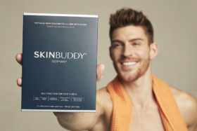 A man holding a box of SKINBUDDY Facial mask for bearded man in front
