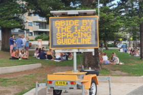 """An LED sign with """"Abide by the 1.5 m spacing guideline"""" message"""