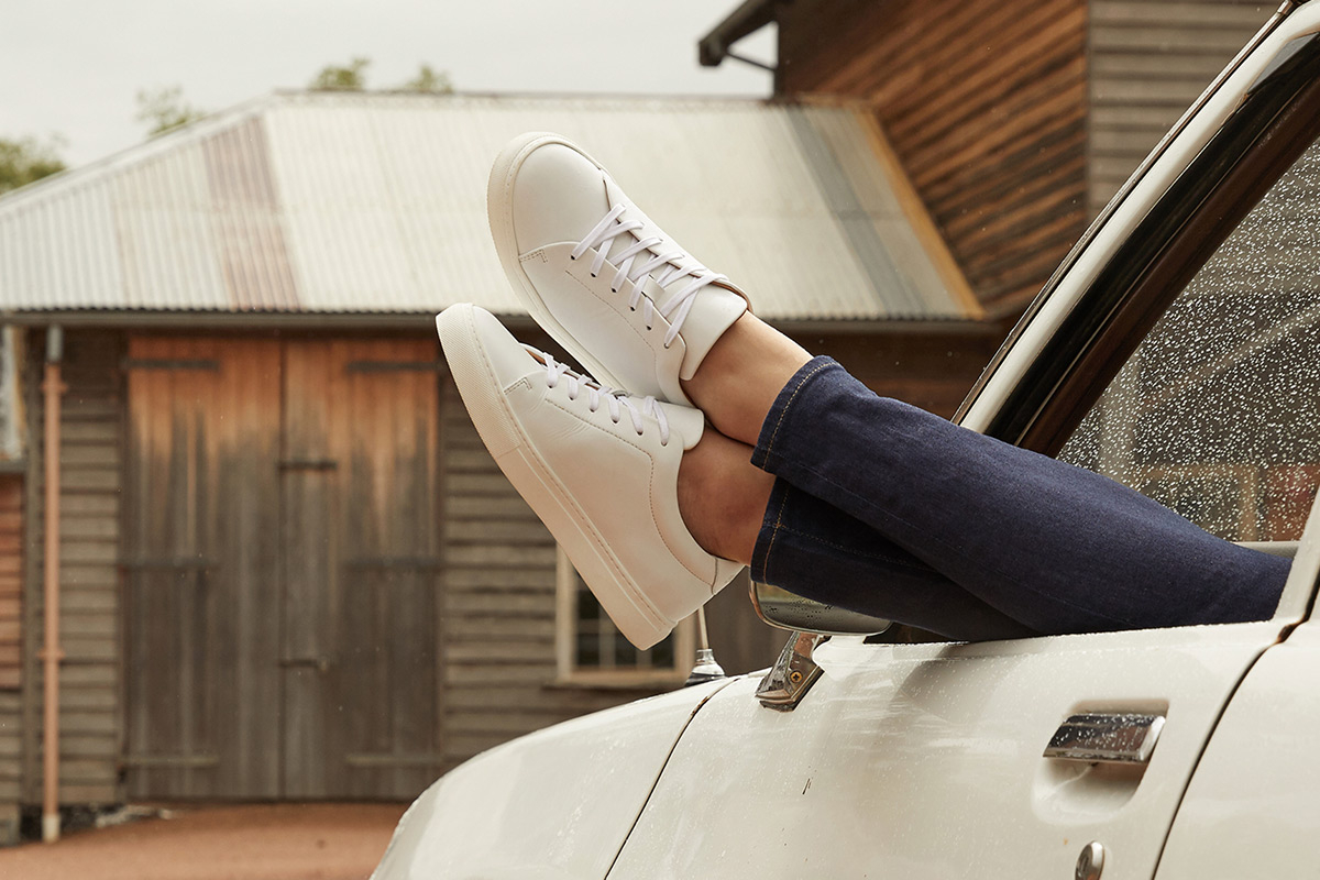 Two feet wearing white R.M. Williams Sneakers