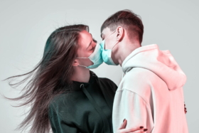 A man and woman kissing with masks on