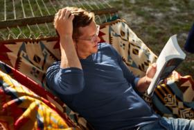 A model in a hammock reading a book wearingFisher+Baker t-shirt