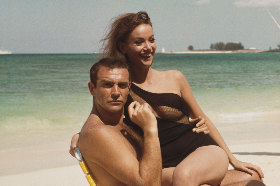 Claudine Auger in a black swimsuit sitting on lap of Sean Connery in a chair