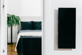 A bedroom andKOLEDA SOLUS+ heater on a wall