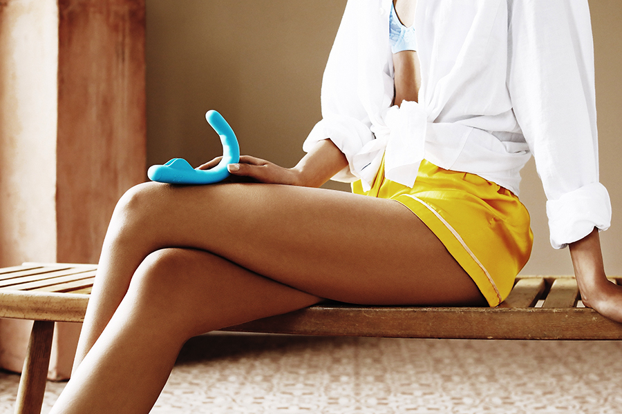 A sitting woman in yellow shorts and white shirt holding MysteryVibe Crescendo on her knee