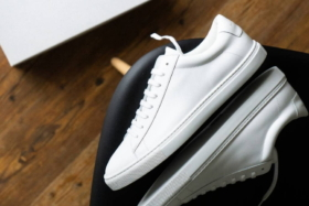 A pair of white Oliver Cabell sneakers on their side with their soles touching