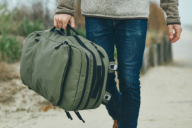 Pakt Travel Backpack in a man's hand
