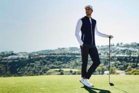 A golfer in a white full-sleeve t-shirt under black sleeveless jacket