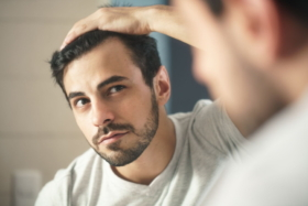 A man looking at his hairline in mirror