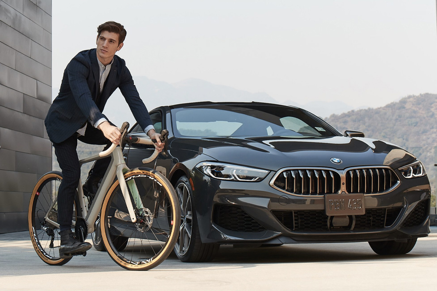 Man on3T X BMW Exploro Bicycle next to a BMW car