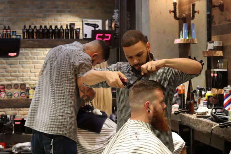 Barbers cutting hair of customers