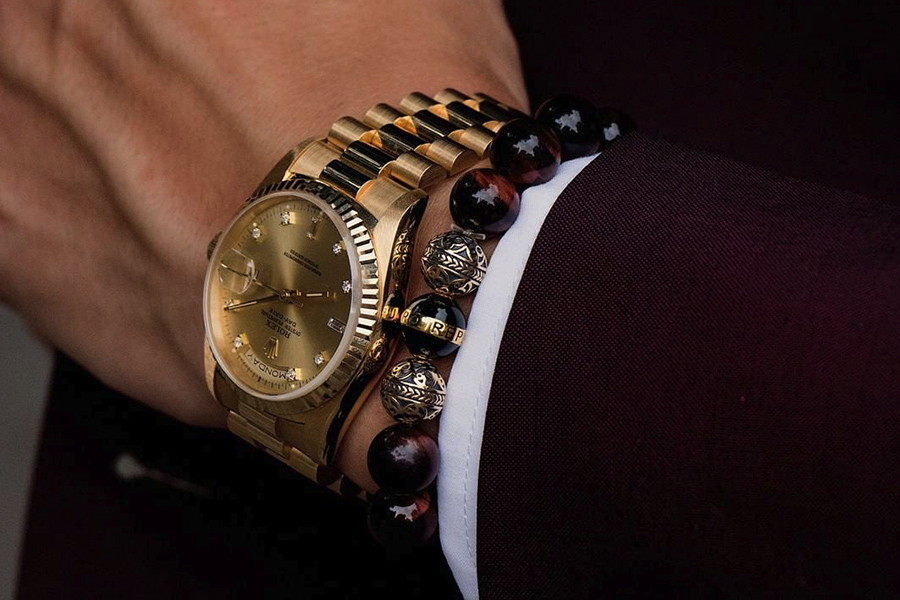 A man's wrist with Rolex watch and Azuro Republic beaded bracelet