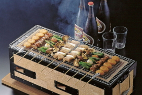 Food skewers on a Hibachi grill and bottles of beer