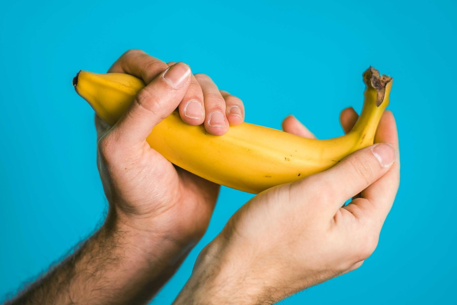A pair of hands holding a banana
