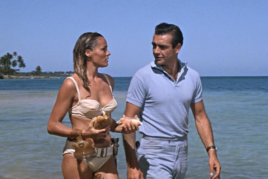 A man and a woman in bikini walking on a beach