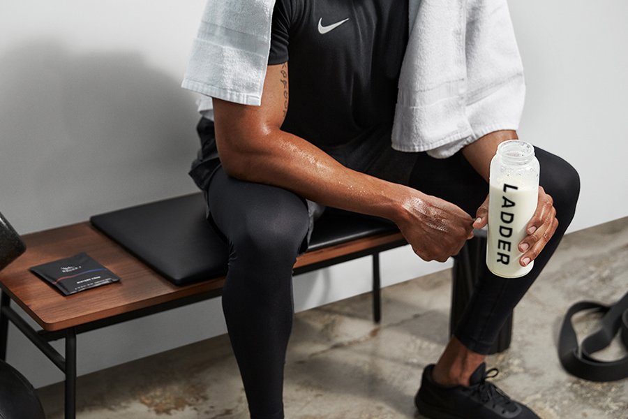 A man at gym bench holding LADDER bottle
