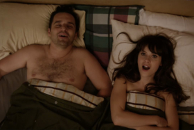 A movie scene with a surprised actress and happy actor in bed