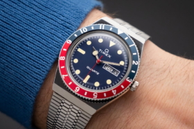 A red and blue Q TImex watch on a wrist