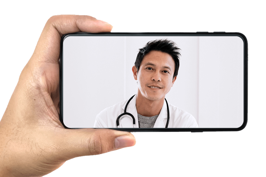 A hand holding a phone with a doctor on screen