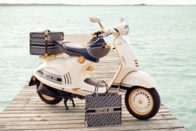 Vespa 946 Christian Dior edition and a Christian Dior bag on a wooden deck with water in background