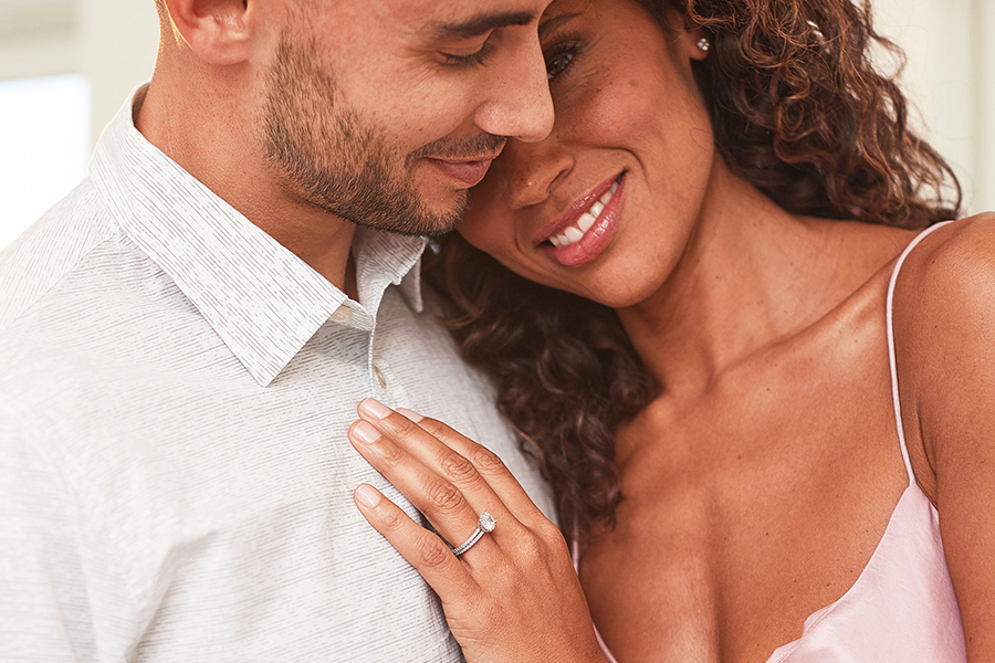 A woman with an engagement ring leaning on shoulder of a man