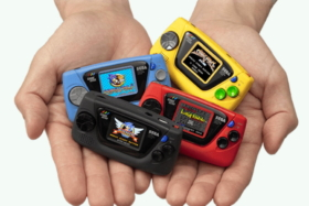 A pair of hands with four Sega Game Gear Micros in joined palms