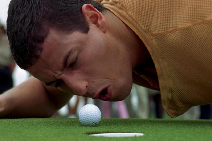 A man trying to push a golf ball by blowing air out of mouth