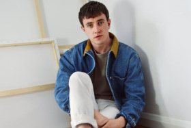 A model in a denim jacket and white pants