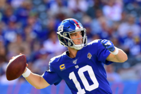 Eli Manning in his football gear throwing a football