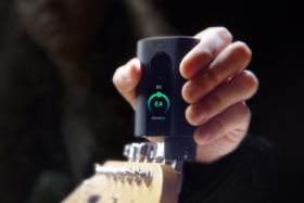 A hand tuning a guitar with Roadie 3 showing B3 E4