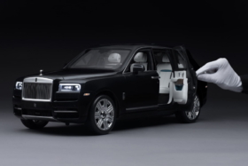 A hand in white glove holding an open door of Rolls Royce Cullinan Replica
