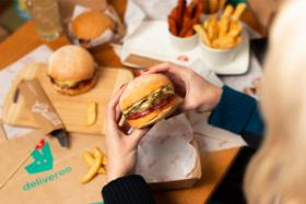 A pair of hands holdingThe Brisket Cheeseburger