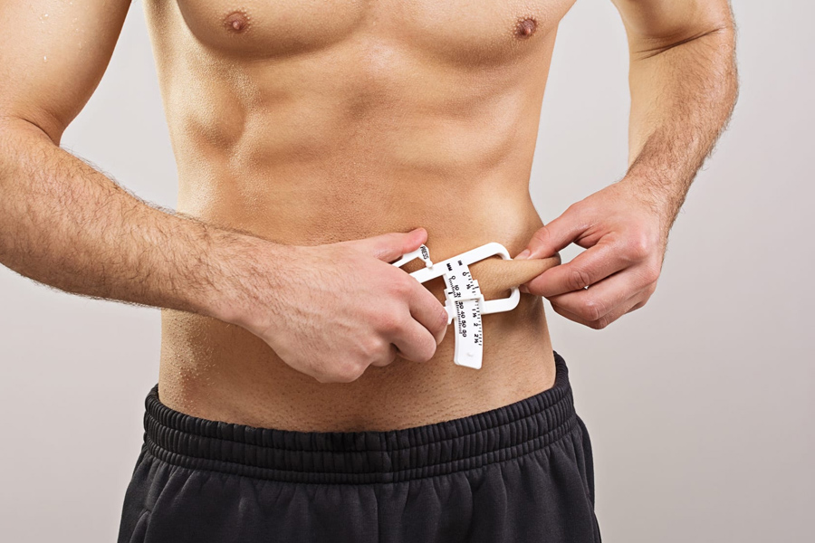 A man measuring belly flab thickness with a skin fold calipe