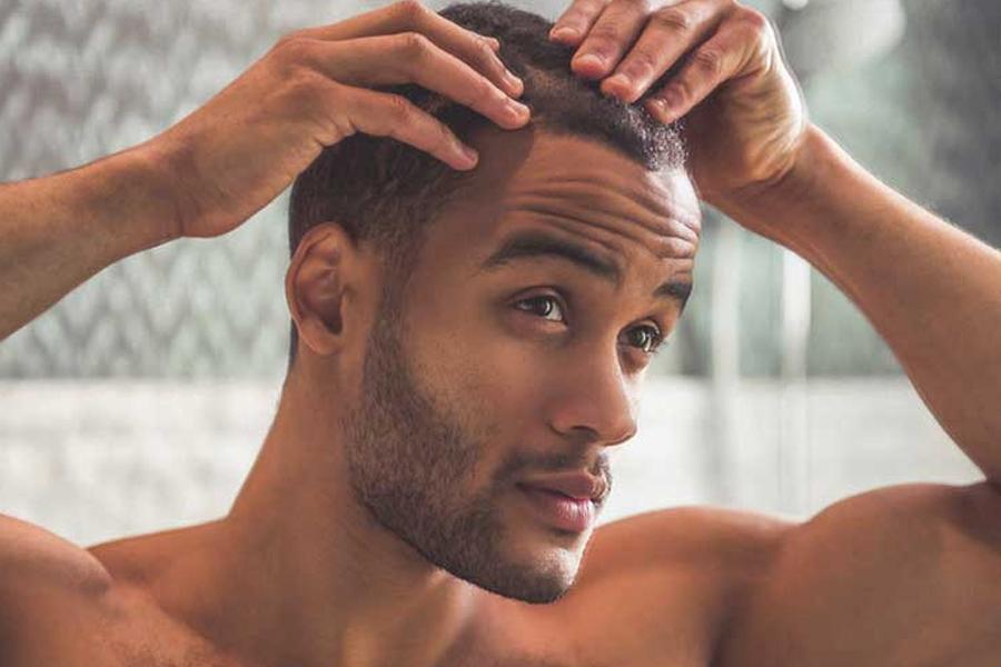 A man checking his scalp in mirror