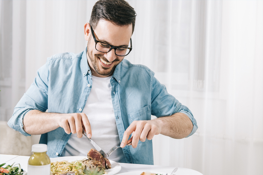 Man smiling and cutting the food on table