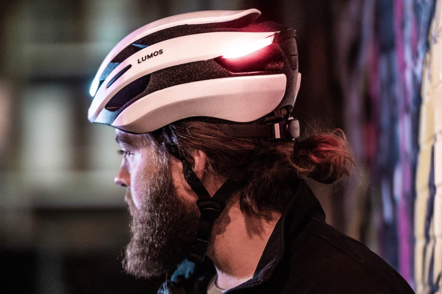Profile of a man wearing red and white Lumos helmet