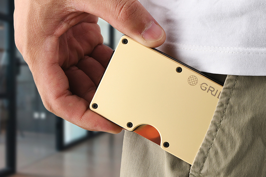 A hand putting Grid wallet in pant pocket