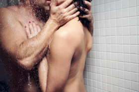 Bare-chested man and woman kissing in shower