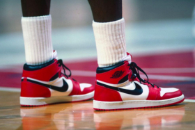 Feet of a basketball player wearing red Air Jordans on court
