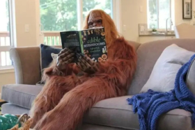 Man dressed as Bigfoot sitting on a sofa and reading a book titled Edible Mushrooms