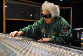An old woman on a music system wearing silver headphones and black glasses