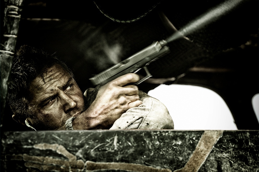 Tom Hardy shooting with a gun from Mad Max Fury Road