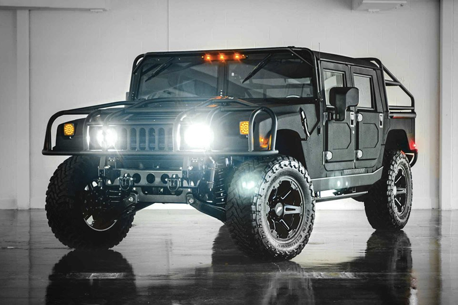 Three quarters front of Mil-Spec's Hummer H1 with headlights on