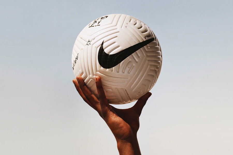 A hand holding a Nike Flight football