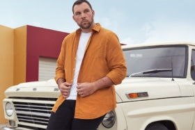 A model leaning on front hood of a Ford truck wearing an orange shirt over a white t-shirt from Johnny Bigg