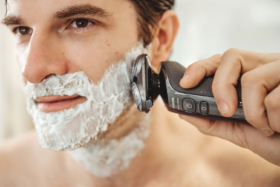 A man shaving his beard with Philips Series 6000 shaver
