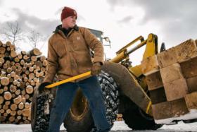 A lumberjack with a hammer wearing a Carhartt jacket