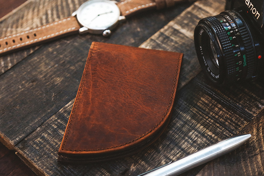 Rogue Front Pocket Leather Wallet on a wood table with watch and camera
