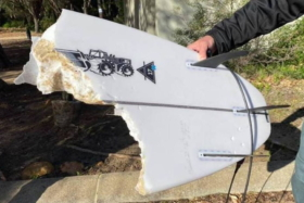 A hand holding a broken white surfboard