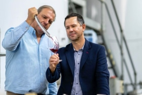 A man pouring wine in Ricky Ponting's glass from wine thief